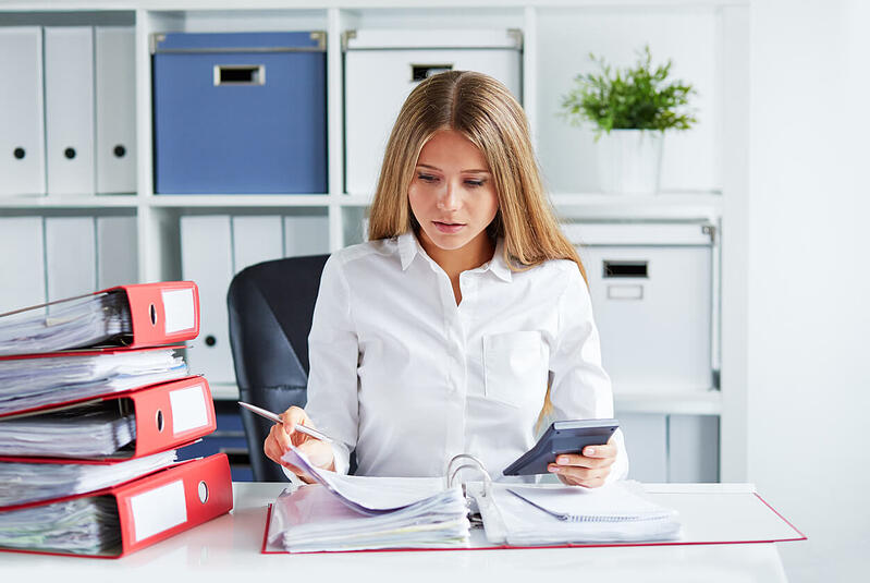 A Woman Sitting at a Desk Holding a Calculator and Looking in a Ring Binder
